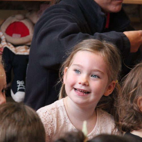 Little girl smiling in crowd of children