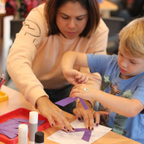Little boy and parent making craft together