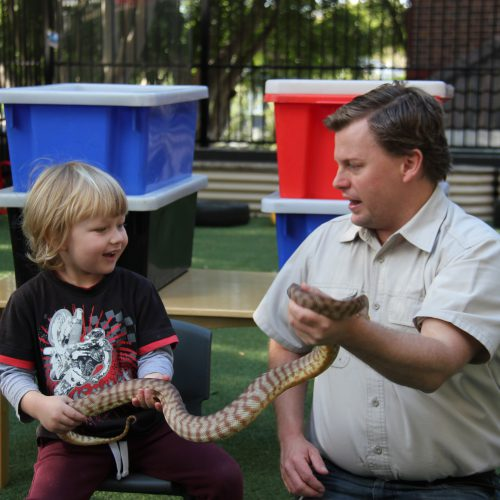 Boy and wildlife man holding snake together