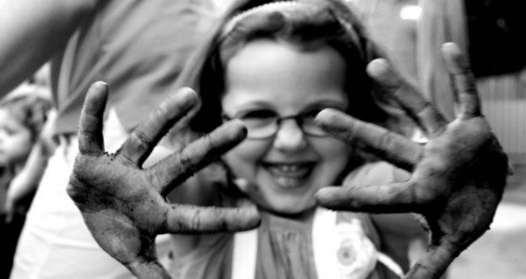 Muddy hands of little girl